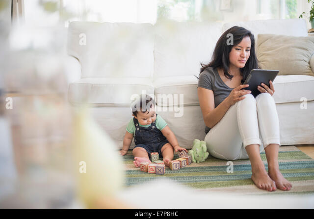 Mother using tablet pc while her son (6-11 months) playing with building blocks - Stock-Bilder