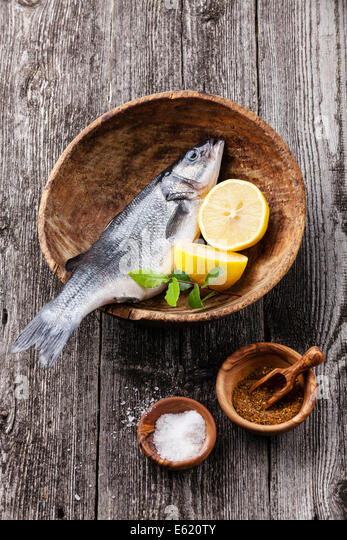 Fresh raw fish seabass with salt, spices and lemon on textured wooden background - Stock Image