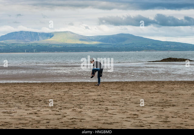 Lady decides barefoot is better than sandy shoes on Newborough Beach - Stock Image