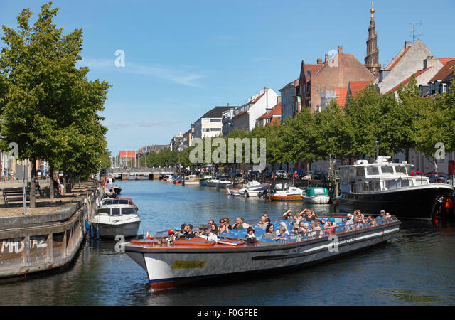 Canal cruise boat in Christianshavn's Canal  turning towards the main harbour canal. View of spire of Church - Stock Image