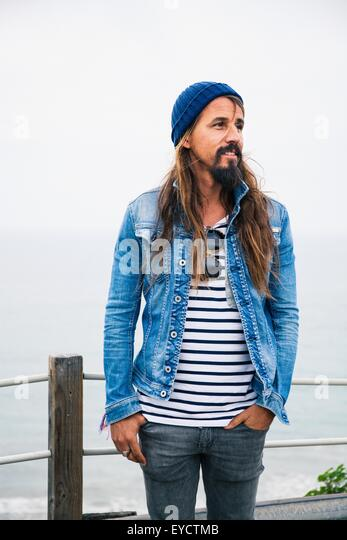 Mid adult man wearing denim jacket and striped top - Stock Image