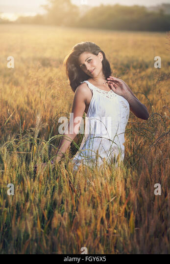Portrait of a beautiful woman in a field. Summer sunset light - Stock-Bilder