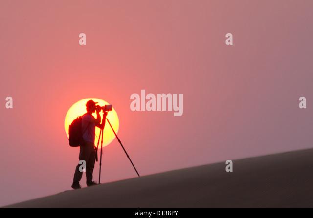 Photographer silhouetted in the setting sun in the Namib Desert, Namibia - Stock-Bilder
