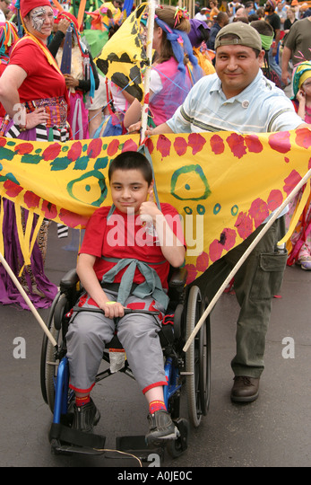 Cleveland Ohio University Circle Parade the Circle costumes masks Hispanic disabled boy wheelchair father - Stock Image