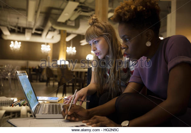 Serious female designers working late at laptop in office - Stock Image