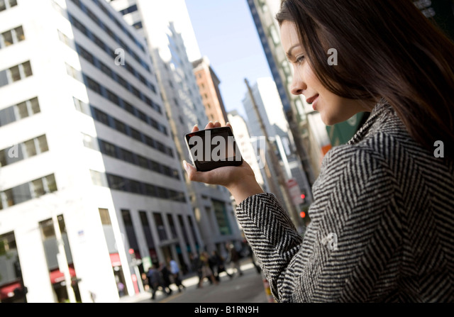 A young woman is located in a downtown city area carrying a hand held computerized device. - Stock Image