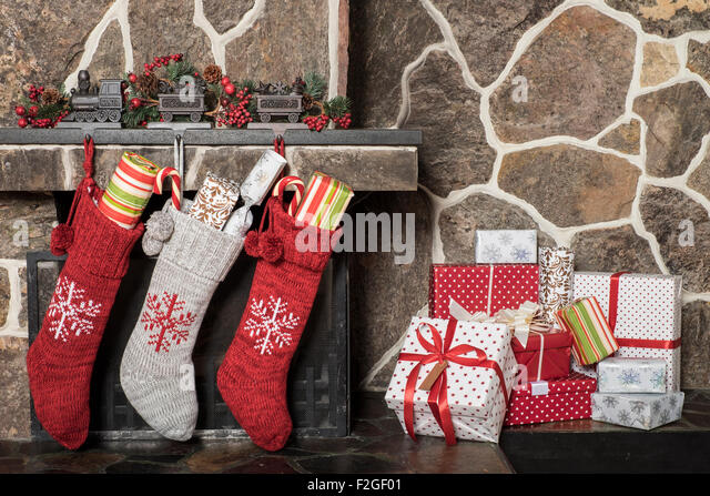 Stuffed stockings hanging on a fireplace on christmas morning - Stock Image