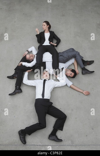 Businessman lifting colleagues, elevated view - Stock Image