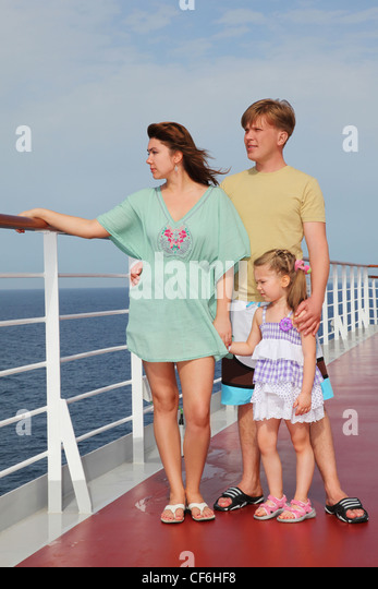 family with daughter standing on cruise liner deck, full body, looking left - Stock Image