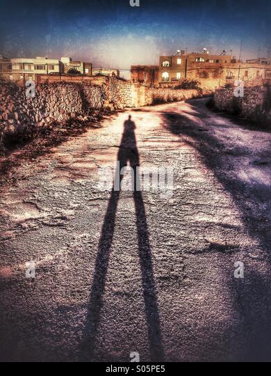 Shadow of male stretching up a country road at dawn - Stock Image