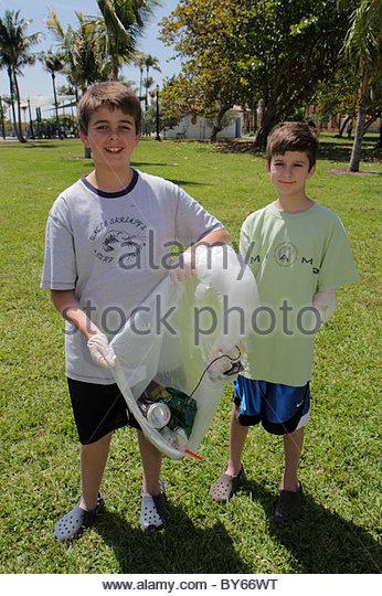 Miami Beach Florida Marjory Stoneman Douglas Park volunteer student boy brothers trash bag litter pick up - Stock Image