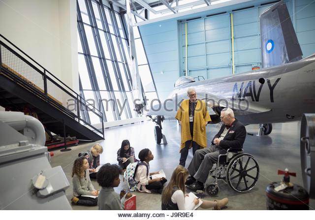 Docent and war veteran talking to students on field trip at Naval airplane in war museum hangar - Stock-Bilder