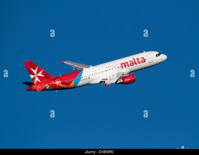Commercial air travel. Air Malta Airbus A320 jet plane climbing on departure against a clear blue sky - Stock-Bilder