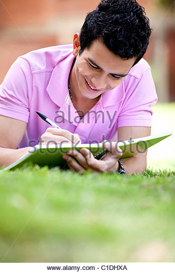 Casual guy studying outdoors lying on the floor - Stock Image