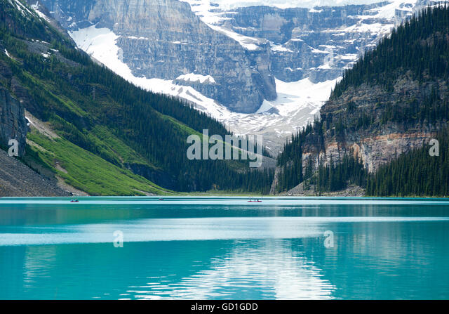 People rowing on canoes in Lake Louise in Alberta, Canada. The summer waters are still and the mountains in the - Stock Image