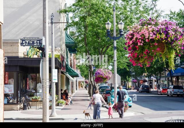 Wisconsin Kenosha Sixth 6th Avenue shopping district man woman flower planter cross street intersection girl parents - Stock Image