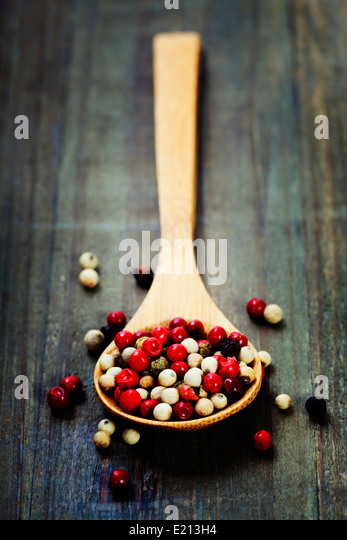 Peppercorn mix in wooden spoon - Stock Image