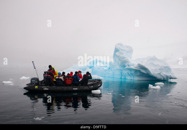 Tourists in a Zodiac crusing through icebergs, Enterprise Island, Antarctica, Polar Regions - Stock Image