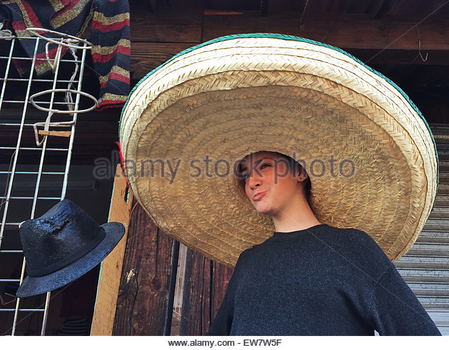 Girl wearing a giant sombrero in a market, Mexico - Stock Image