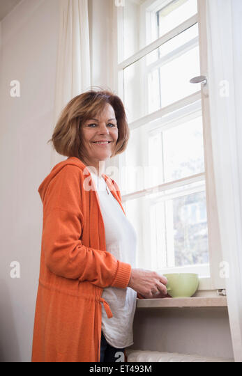 Side profile of senior woman smiling with having cup of tea at home, Munich, Bavaria, Germany - Stock-Bilder