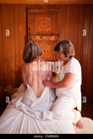 Mature massage therapist and mature client. - Stock Image
