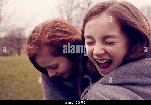 Young friends wrapped in a blanket and laughing outdoors - Stock Image