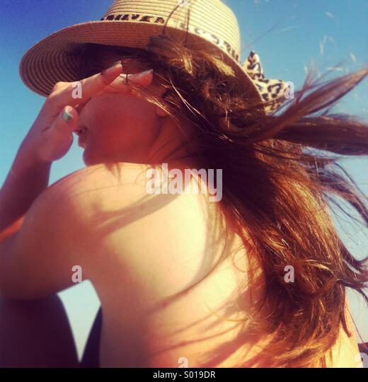 Young beautiful women with long dark hair and hat on the beach - Stock-Bilder