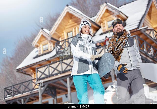 Snowboarder couple carrying snowboards below sunny cabin - Stock-Bilder