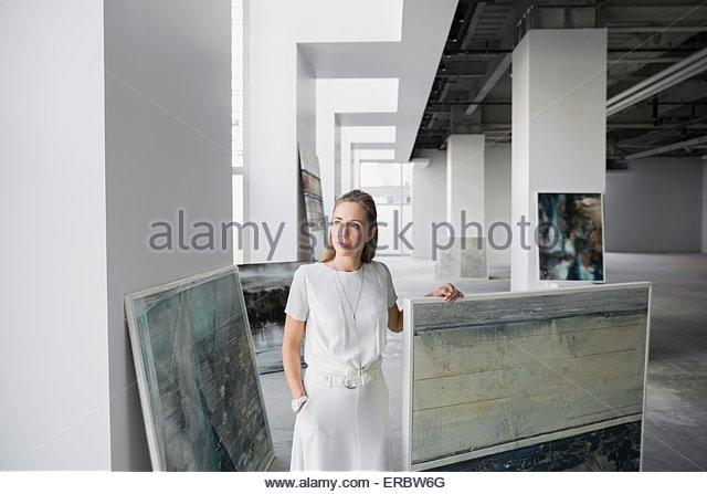 Pensive art dealer with paintings in art gallery - Stock-Bilder