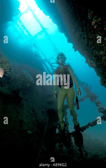 Underwater interior hold diver exploring interior of sunken ship - Stock Image