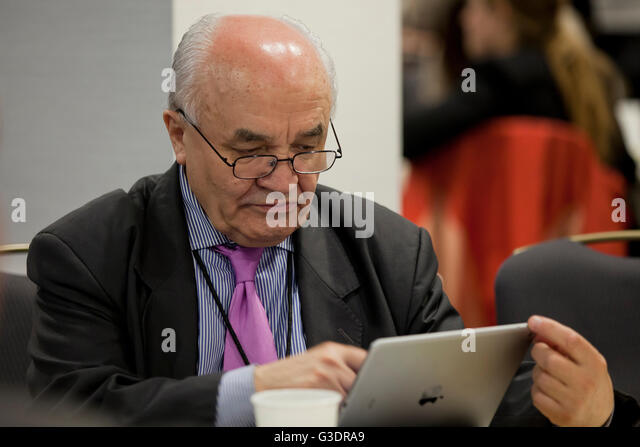 Middle aged man using an iPod in office - USA - Stock Image