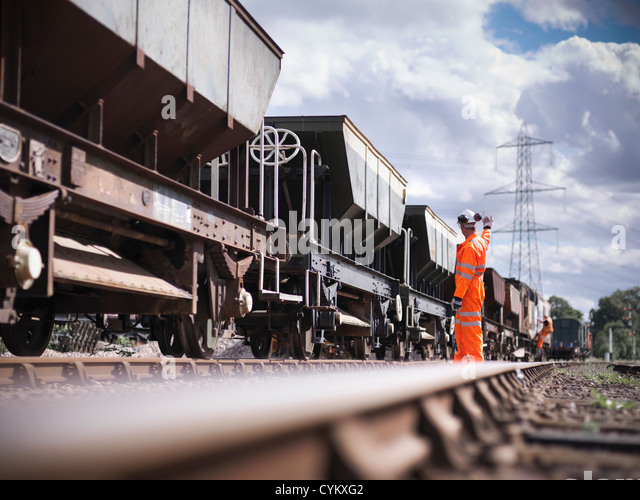 Railway workers signaling train - Stock Image