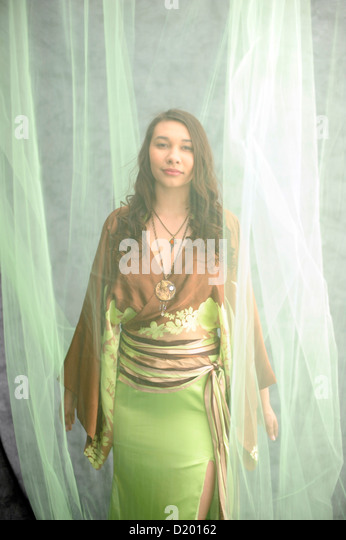 Beautiful young woman dressed in a modern spring kimona gown veiled in soft green tule. - Stock Image
