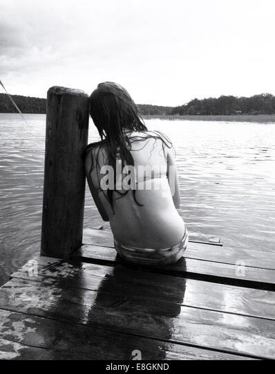 Girl sitting on a jetty after a swim, Stockholm, Sweden - Stock Image