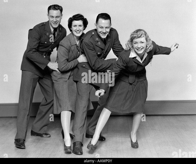 1940s CONGA LINE TWO MEN SOLDIERS AND TWO WOMEN DANCING SMILING LOOKING AT CAMERA - Stock Image