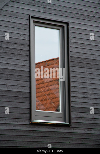 Window reflecting roof tiles - Stock Image