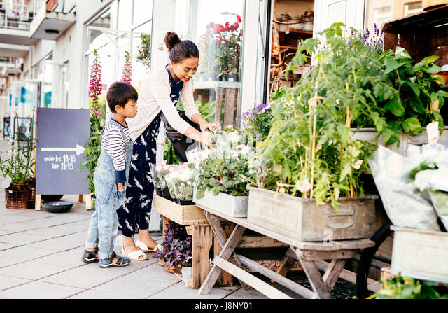 Mother with son (4-5) choosing plants - Stock-Bilder