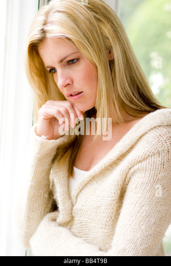 Woman looking sad out of window - Stock Image