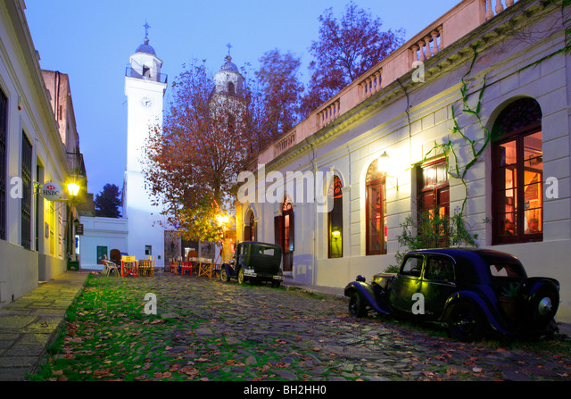 Old street at Colonia del sacramento, with old car and cathedral. uruguay, south america. - Stock Image