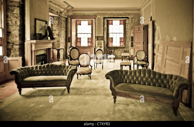 a collection of chairs and sofas in a run down room - Stock Image