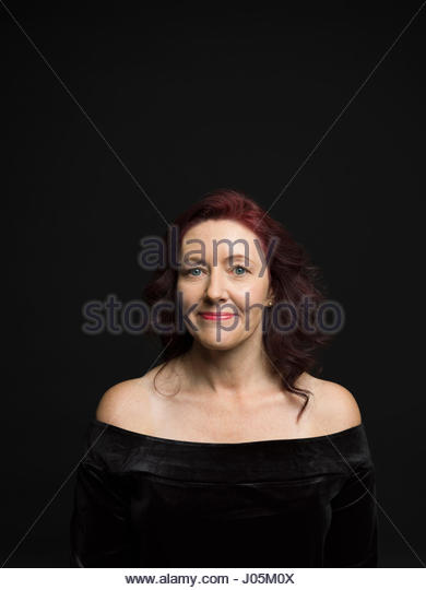 Portrait smiling woman with bare shoulders and red hair against black background - Stock Image