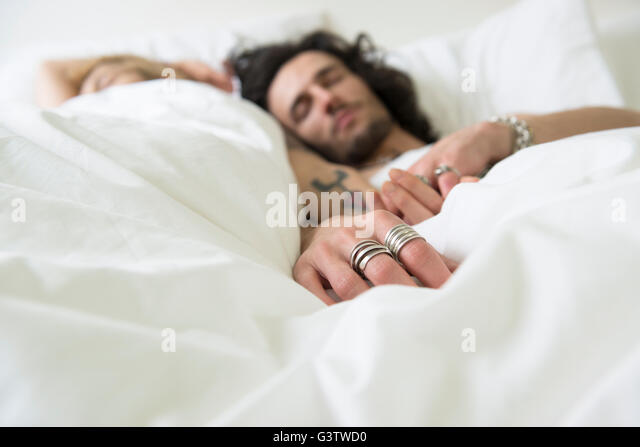A cool young couple relaxing in bed with their eyes shut. - Stock-Bilder
