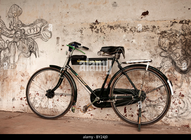 India, Cochin. A bike leans against an artistically-graffitied wall. - Stock-Bilder