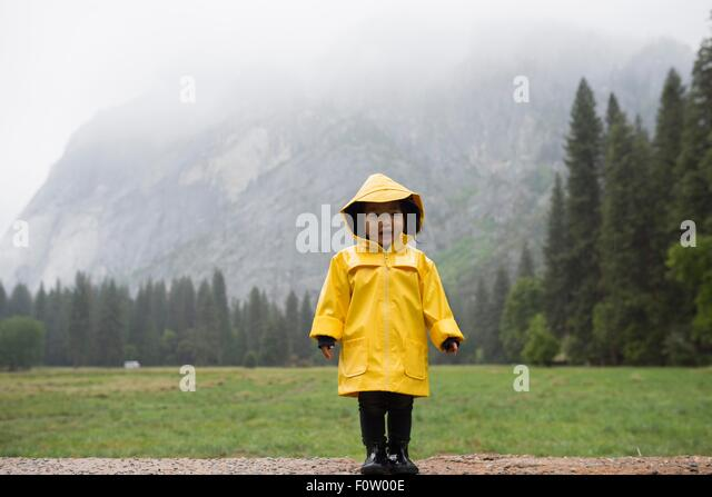 Portrait of female toddler wearing yellow raincoat in front of misty mountain, Yosemite National Park, California, - Stock Image