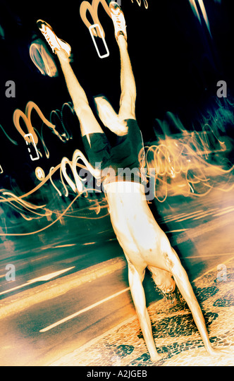Male age 20-25 doing a handstand at night in Brazil.The Image shows light movements in the background. - Stock Image