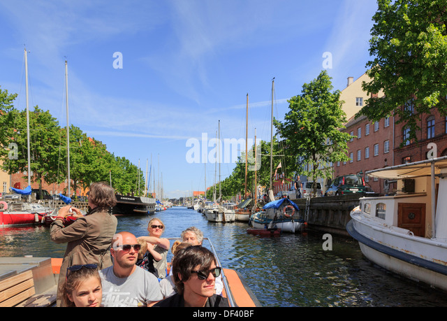 Tourists' sightseeing cruise boat on the Christianshavns Kanal, Overgaden, Christianshavn, Copenhagen, Zealand, - Stock Image