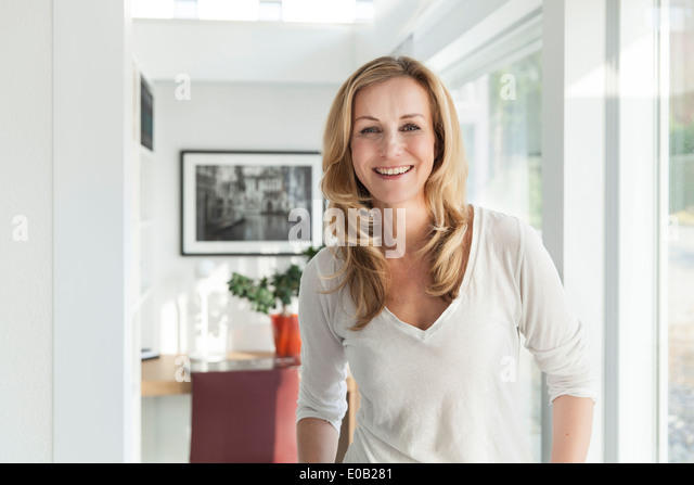 Portrait of happy woman standing in her bright modern home - Stock Image