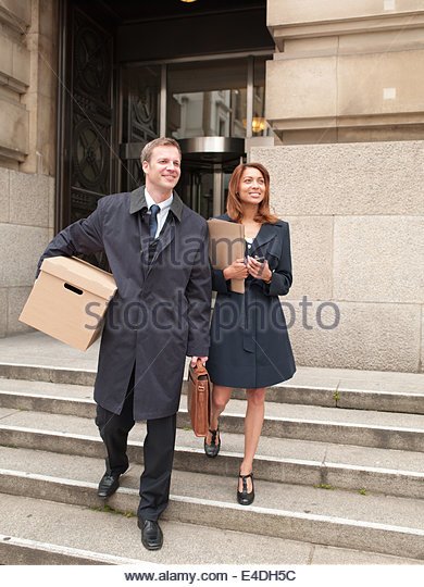 Lawyers leaving courthouse with files and box - Stock-Bilder