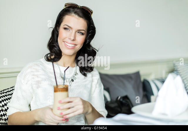 Beautiful young  lady smiling in a restaurant while holding her coffee - Stock Image