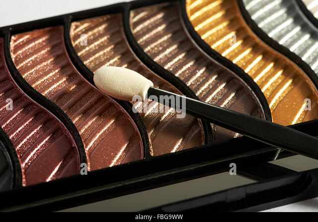Close up view of compact makeup case with applicator on top of various eye shadow colors - Stock Image